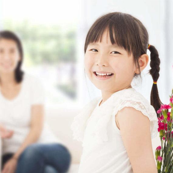 そばにいるお母さんにプレゼントする花を背中に隠して、こちらを向いて笑っている子供のころの私