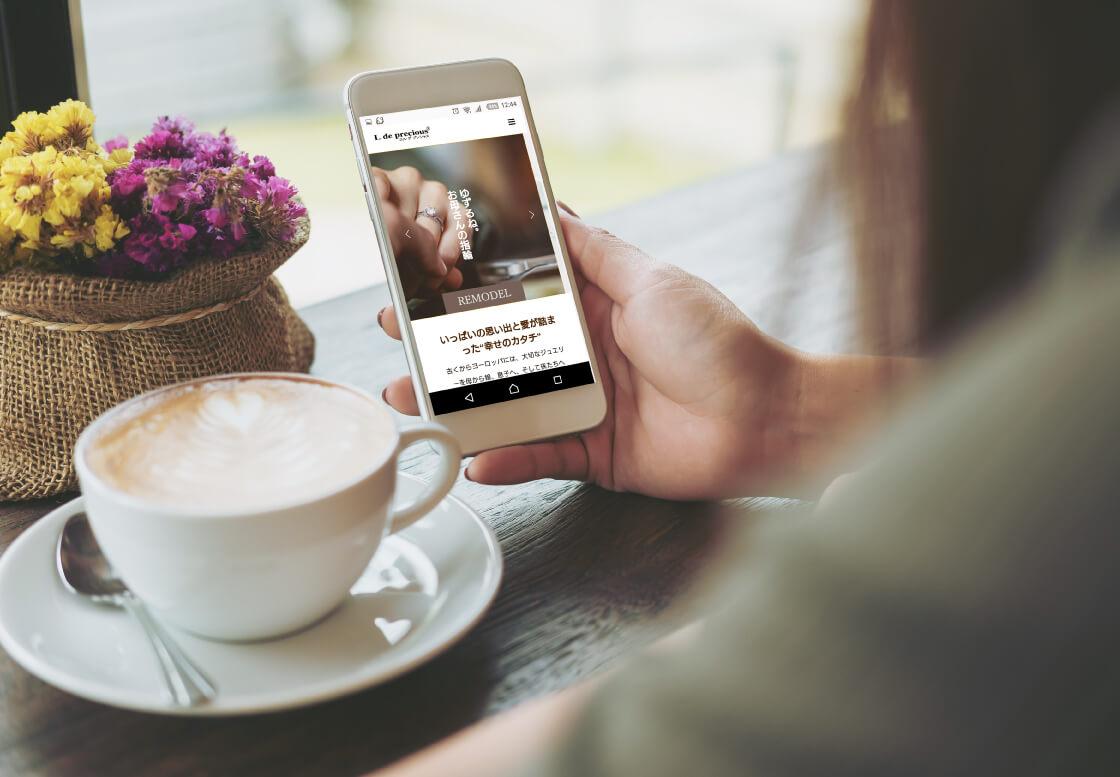 カフェでお茶しながら、スマートフォンでエルデプレシャスのリモデルのホームページを閲覧している様子