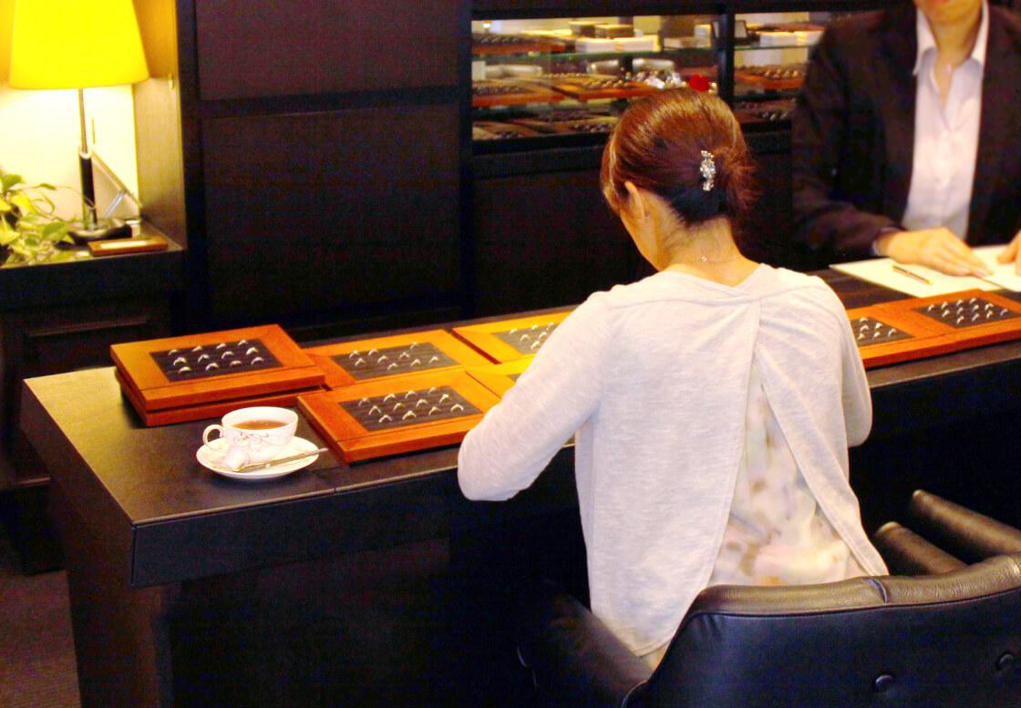ゆっくりとデザインを選んでいる女性の後ろ姿と、店内の様子